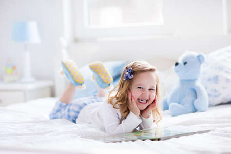 cama: Funny girl niño feliz leyendo un libro y jugando con su juguete oso de peluche en la cama. Los niños juegan en casa. Guardería Blanca. Niño en el dormitorio soleado. Los niños leen y el estudio. Interior para el bebé y niño pequeño.