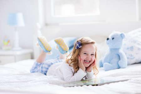 dzieci: Funny szczęśliwy maluch dziewczyna czyta książkę i gry z jej zabawki misia w łóżku. Dzieci grać w domu. Biały przedszkola. Dziecko w słonecznej sypialni. Dzieci czytać i studiować. Wnętrze dla dziecka i młodego dzieciaka.