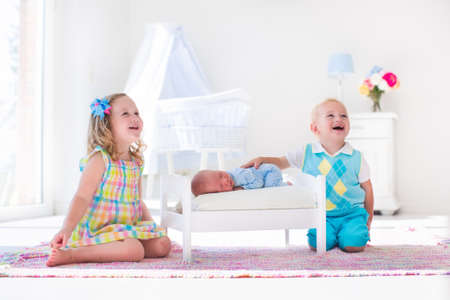 cute girl: Cute little boy and girl kissing newborn brother. Toddler kids meet new born sibling at home. Infant sleeping in toy bed in white nursery. Kids playing and bonding. Children with small age difference. Stock Photo