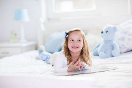 chambre � coucher: Dr�le enfant fille heureuse de lire un livre et en jouant avec son jouet ours en peluche dans un lit. Les enfants jouent � la maison. P�pini�re blanc. Enfant dans la chambre ensoleill�e. Les enfants lisent et l'�tude. Int�rieur pour b�b� et jeune enfant. Banque d'images