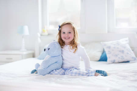 baby bedroom: Funny happy toddler girl reading a book and playing with her toy teddy bear in bed. Kids play at home. White nursery. Child in sunny bedroom. Children read and study. Interior for baby and young kid.