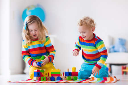 preschooler: Children playing with wooden train. Toddler kid and baby play with blocks, trains and cars. Educational toys for preschool and kindergarten child. Boy and girl build toy railroad at home or daycare.