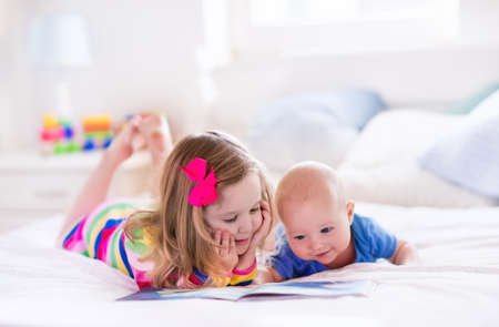 bedtime story: Funny happy toddler girl reading a book and playing with newborn baby boy in bed. Kids play at home. White nursery. Child in sunny bedroom. Children read and study. Interior for baby and young kid.