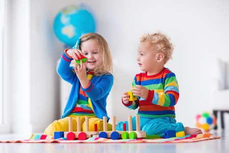 Enfants jouant avec un train en bois. Enfant en bas âge et le bébé jouer avec des blocs, trains et voitures. Jouets éducatifs pour les enfants d'âge préscolaire et à la maternelle. Garçon et fille construction jouet chemin de fer à la maison ou à la garderie. Banque d'images - 49114770