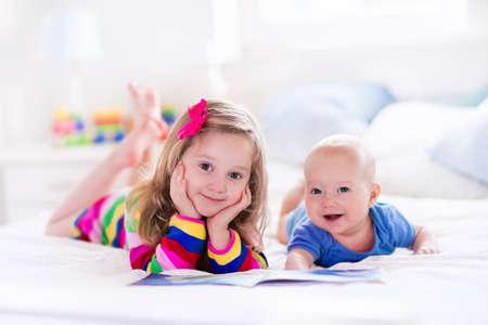 garderie: Drôle enfant fille heureuse de lire un livre et en jouant avec nouveau-né dans le lit. Les enfants jouent à la maison. Pépinière blanc. Enfant dans la chambre ensoleillée. Les enfants lisent et l'étude. Intérieur pour bébé et jeune enfant. Banque d'images