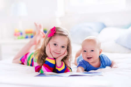 Funny happy toddler girl reading a book and playing with newborn baby boy in bed. Kids play at home. White nursery. Child in sunny bedroom. Children read and study. Interior for baby and young kid.