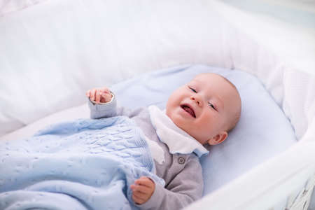 cable knit: Newborn baby boy in bed. New born child sleeping under a white knitted blanket. Children sleep. Bedding for kids. Infant napping in bed. Healthy little kid shortly after birth. Cable knit textile.