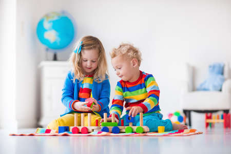 kindergarten toys: Children playing with wooden train. Toddler kid and baby play with blocks, trains and cars. Educational toys for preschool and kindergarten child. Boy and girl build toy railroad at home or daycare.