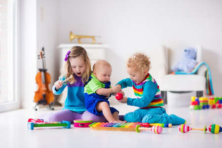 xylophone: Children with music instruments. Musical education for kids. Colorful wooden art toys. Little girl and boy play music. Kid with xylophone, guitar, flute, violin. Early development for toddler and baby Stock Photo