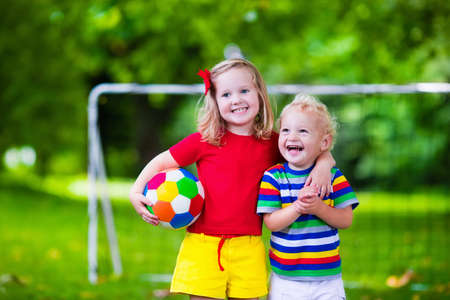 Twee gelukkige kinderen spelen Europees voetbal in openlucht in schoolplein. Kinderen voetballen. Actieve sport voor voorschoolse kind. Ball spel voor jong kind team. Jongen en meisje een doelpunt in de voetbalwedstrijd. Stockfoto - 49486234