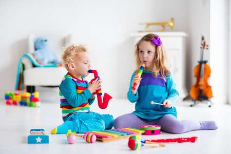 Kinderen met muziek instrumenten. Muzikaal onderwijs voor kinderen. Kleurrijke houten kunst speelgoed. Meisje en jongen te spelen muziek. Kid met xylofoon, gitaar, fluit, viool. Vroege ontwikkeling voor peuter en baby