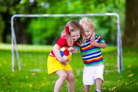 enfant qui joue: Deux enfants heureux de jouer football européen en plein air dans la cour d'école. Les enfants jouent au soccer. Sport actif pour enfant d'âge préscolaire. Ball jeu pour jeune équipe d'enfant. Garçon et fille marquer un but dans le match de football. Banque d'images