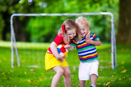balones deportivos: Dos niños felices jugando fútbol europeo al aire libre en el patio de la escuela. Los niños juegan al fútbol. Deporte activo para el niño preescolar. Juego de bola para el joven equipo chico. Niño y niña marcar un gol en el partido de fútbol. Foto de archivo