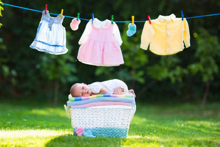 Newborn baby on a pile of clean dry towels. New born child after bath in a towel. Family washing clothes. Kids wear hanging on a line outdoors in summer garden. Infant apparel, textile for children.