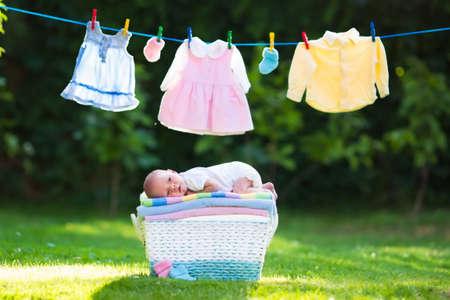 ropa de verano: Bebé recién nacido en una pila de toallas limpias y secas. Nueva niño nacido después del baño en una toalla. Lavar la ropa de la familia. Niños desgaste colgando de una línea al aire libre en el jardín de verano. Ropa infantil, textil para niños. Foto de archivo