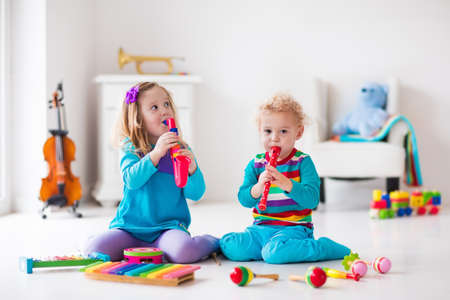 Children with music instruments. Musical education for kids. Colorful wooden art toys. Little girl and boy play music. Kid with xylophone, guitar, flute, violin. Early development for toddler and baby Stock Photo