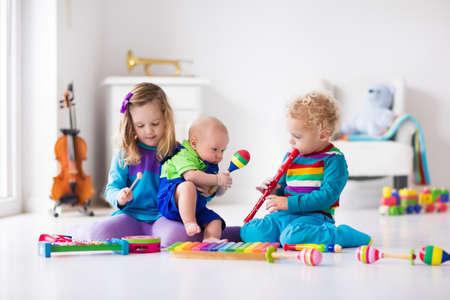 乳幼児: 楽器と子どもたち。子供のための音楽教育。カラフルな木製アートのおもちゃ。少女と少年は、音楽を再生します。木琴、ギター、フルート、ヴァイオリンとの子