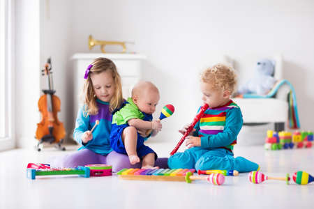 Children with music instruments. Musical education for kids. Colorful wooden art toys. Little girl and boy play music. Kid with xylophone, guitar, flute, violin. Early development for toddler and baby 免版税图像