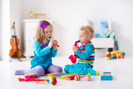 Children with music instruments. Musical education for kids. Colorful wooden art toys. Little girl and boy play music. Kid with xylophone, guitar, flute, violin. Early development for toddler and baby Foto de archivo