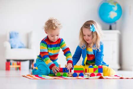 Kinder spielen mit Holzeisenbahn. Kleinkind Kind und Baby spielen mit Blöcken, Zügen und Autos. Pädagogische Spielwaren für Kinder im Vorschul und Kindergartenkind. Junge und Mädchen bauen Spielzeug-Eisenbahn zu Hause oder Kindertagesstätte. Standard-Bild