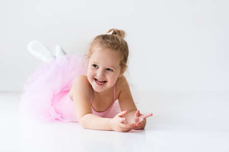 elegant girl: Little ballerina girl in a pink tutu. Adorable child dancing classical ballet in a white studio. Children dance. Kids performing. Young gifted dancer in a class. Preschool kid taking art lessons.