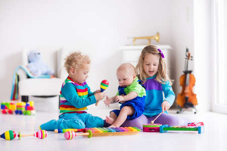 Children with music instruments. Musical education for kids. Colorful wooden art toys. Little girl and boy play music. Kid with xylophone, guitar, flute, violin. Early development for toddler and baby Imagens