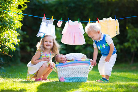 Niño recién nacido en una pila de toallas limpias y secas. Hermano y hermana besando pequeño hermano. Hermanos unión. Los niños y ropa de bebé en línea del lavadero y cesta. Los niños que juegan al aire libre en el jardín de verano