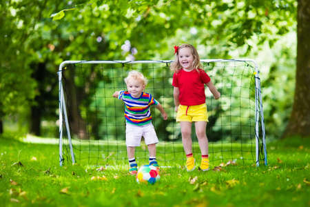 child sport: Two happy children playing European football outdoors in school yard. Kids play soccer. Active sport for preschool child. Ball game for young kid team. Boy and girl score a goal in football match.