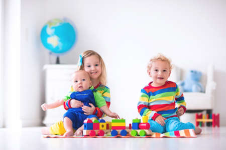infant school: Children playing with wooden train. Toddler kid and baby play with blocks, trains and cars. Educational toys for preschool and kindergarten child. Boy and girl build toy railroad at home or daycare.