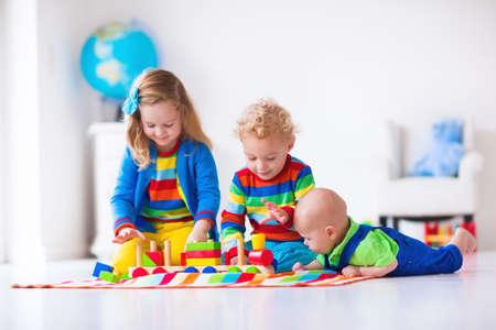 kinder: Niños jugando con el tren de madera. Niño niño y el bebé juegan con bloques, trenes y coches. Juguetes educativos para preescolar y jardín de infantes menores. El muchacho y la estructura de la muchacha ferrocarril del juguete en casa o en la guardería.