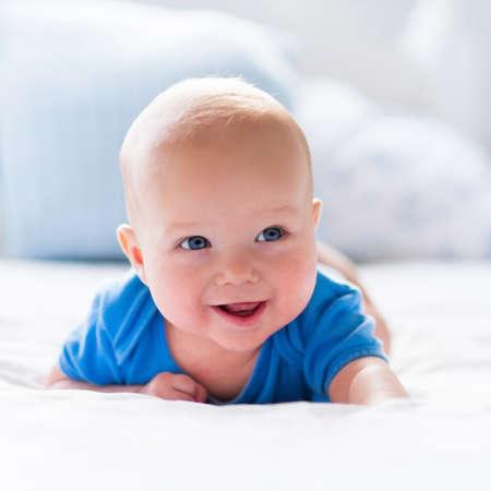 흰색 맑은 침실에서 사랑스러운 아기 소년. 침대에서 편안한 신생아. 어린 아이들을위한 보육. 섬유 및 아이들을위한 침구. 집에서 가족 아침. 장난감
