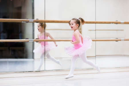 classes: Little ballerina girl in a pink tutu. Adorable child dancing classical ballet in a white studio. Children dance. Kids performing. Young gifted dancer in a class. Preschool kid taking art lessons.