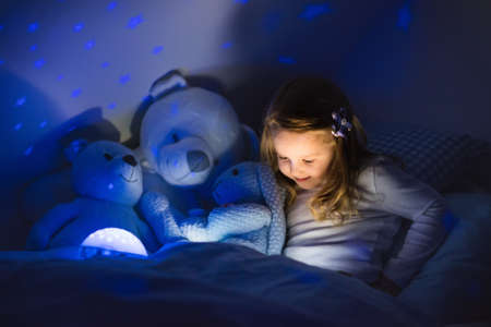 Little girl reading a book in bed. Dark bedroom with night light projecting stars on room ceiling. Kids nursery and bedding. Children read before bedtime. Toddler child playing with lamp and bear toy.