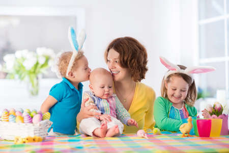 Mother and children painting colorful eggs. Mom, toddler, preschooler and baby with bunny ears paint and decorate Easter egg. Parent and kids play indoors in spring. Family celebrating Easter at home.