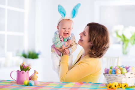 Mother and child painting colorful eggs. Mom and baby with bunny ears paint and decorate Easter egg. Parent and kid play indoors in spring. Decorated home and spring flowers. Family celebrating Easter Stock Photo