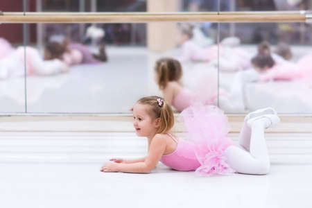 leotard: Little ballerina girl in a pink tutu. Adorable child dancing classical ballet in a white studio. Children dance. Kids performing. Young gifted dancer in a class. Preschool kid taking art lessons.