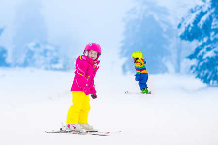 fun: Children skiing in the mountains. Toddler kids in colorful suit and safety helmet learning to ski. Winter sport for family with young child. Kid ski lesson in alpine school. Snow fun for little skier.