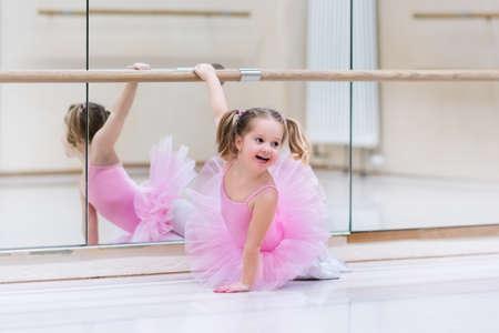 Menina pequena da bailarina em um tutu cor-de-rosa. Criança adorável que dança o bailado clássico em um estúdio branco. Dança de crianças Crianças realizando. Dançarino dotado novo em uma classe. Pré-escolar garoto tendo aulas de arte.