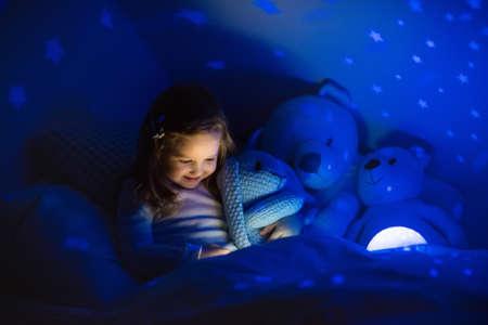 nursery: Niña que lee un libro en la cama. Habitación oscura con luz de noche proyectando estrellas sobre techo de la sala. Guardería niños y ropa de cama. Los niños leen antes de acostarse. Niño pequeño niño jugando con lámpara y oso de juguete.