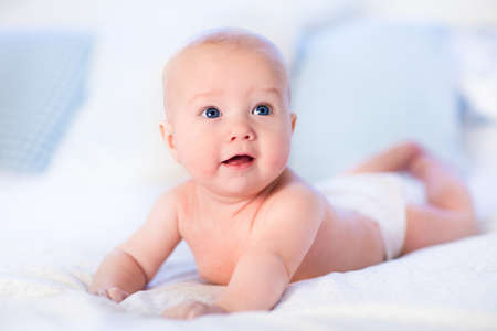 tummy time: Baby boy wearing diaper in white sunny bedroom. Newborn child relaxing in bed. Nursery for children. Textile and bedding for kids. Family morning at home. New born kid during tummy time with toy bear. Stock Photo