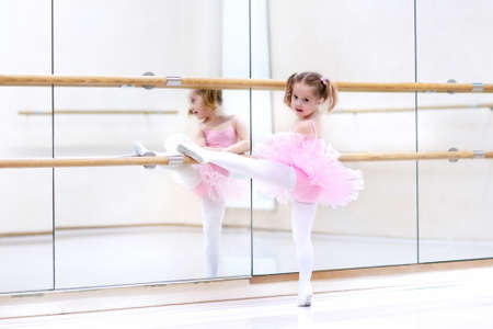 stage costume: Little ballerina girl in a pink tutu. Adorable child dancing classical ballet in a white studio. Children dance. Kids performing. Young gifted dancer in a class. Preschool kid taking art lessons.