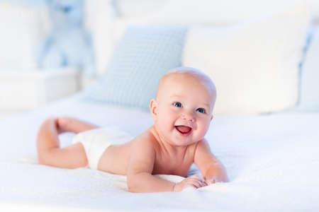 嬰兒: 男嬰穿著紙尿褲在白天晴間臥室。剛出生的孩子在床上放鬆。幼兒園兒童。紡織和床上用品的孩子。家庭早晨在家裡。在趴著的時間與玩具熊新出生的孩子。