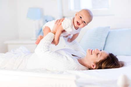 bebes: Madre y niño en una cama blanca. Mamá y bebé en pañales jugando en el dormitorio soleado. Padres y niño descansando en su casa. Familia que se divierten juntos. Ropa de cama y textil para la guardería infantil.