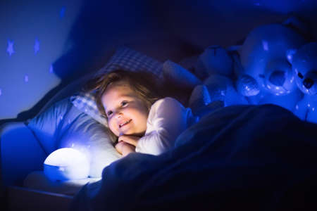 bedrooms: Little girl reading a book in bed. Dark bedroom with night light projecting stars on room ceiling. Kids nursery and bedding. Children read before bedtime. Toddler child playing with lamp and bear toy.