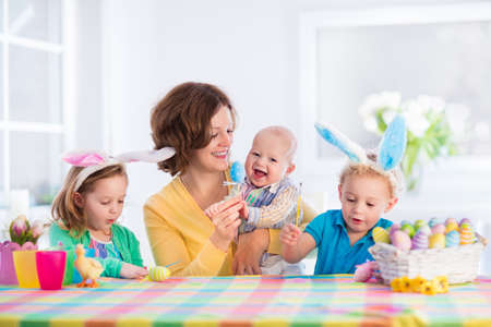 big woman: Mother and children painting colorful eggs. Mom, toddler, preschooler and baby with bunny ears paint and decorate Easter egg. Parent and kids play indoors in spring. Family celebrating Easter at home.