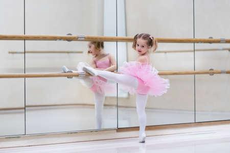 Bambina ballerina in un tutù rosa. Adorabile bambino che balla balletto classico in uno studio bianco. I bambini ballano. L'esecuzione di bambini. Giovane ballerina di talento in una classe. Kid prescolare prendere lezioni d'arte.