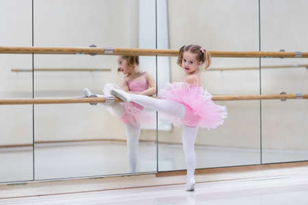 Little ballerina girl in a pink tutu. Adorable child dancing classical ballet in a white studio. Children dance. Kids performing. Young gifted dancer in a class. Preschool kid taking art lessons. Zdjęcie Seryjne - 50840461