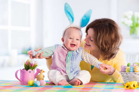 Mother and child painting colorful eggs. Mom and baby with bunny ears paint and decorate Easter egg. Parent and kid play indoors in spring. Decorated home and spring flowers. Family celebrating Easter Foto de archivo