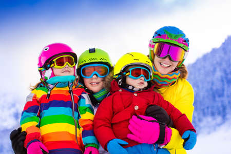 Mother and children skiing in the mountains. Active mom and three kids with safety helmet, goggles and poles. Ski lesson for young children. Winter sport and snow fun for family. Child learning to ski