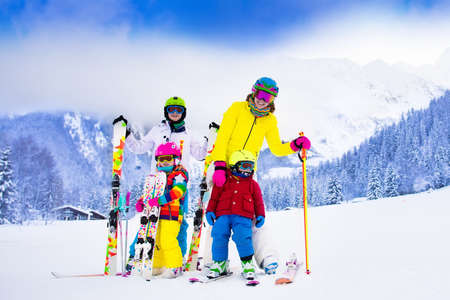 slopes: Mother and children skiing in the mountains. Active mom and three kids with safety helmet, goggles and poles. Ski lesson for young children. Winter sport and snow fun for family. Child learning to ski